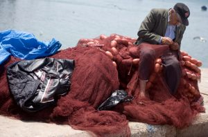 Fisherman mending net.jpg, źródło: Wikimedia commons